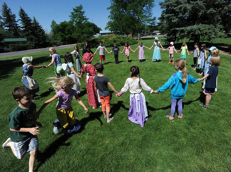 James Enyeart, 6, and Ava Lewis, 8, bottom left, race to get back in to the circle while playing a game called Too Late for Supper on Wednesday, June 15, 2016, at the Lone Tree Schoolhouse at North Lake Park in Loveland. Students participate in activities that are like a typical school day in 1890 during the summer session classes in the one-room schoolhouse. (Photo by Jenny Sparks/Loveland Reporter-Herald)