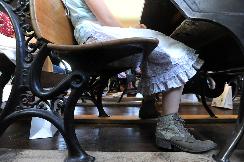 Giana Pascucci, 9, wears an outfit reminiscent of the late 1800's as she sits at her desk Wednesday, June 15, 2016, at the Lone Tree Schoolhouse at North Lake Park in Loveland. Students participate in activities that are like a typical school day in 1890 during the summer session classes in the one-room schoolhouse. (Photo by Jenny Sparks/Loveland Reporter-Herald)