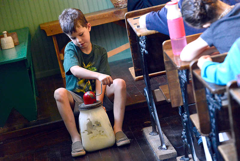 James Enyeart, 6, takes his turn churning butter Wednesday, June 15, 2016, at the Lone Tree Schoolhouse at North Lake Park in Loveland. Students participate in activities that are like a typical school day in 1890 during the summer session classes in the one-room schoolhouse. (Photo by Jenny Sparks/Loveland Reporter-Herald)