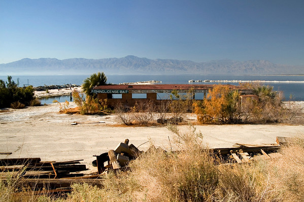 Remnants of a bait-and-tackle shop with the Salton Sea and Santa Rosa Mountains in back.
