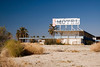 Abandoned motel beneath very blue skies.