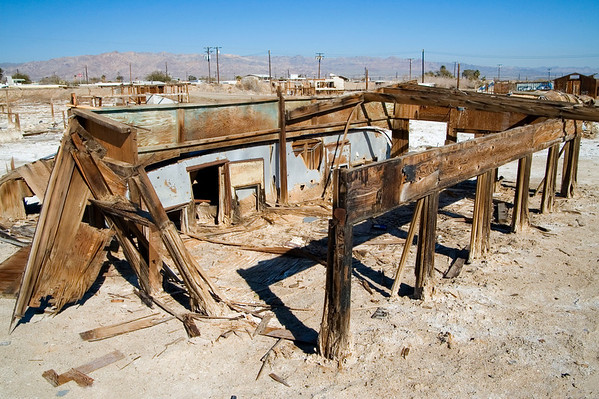 Remnants of yet another former residence with adjacent trailer sunken into the mud and baked by the desert sun.