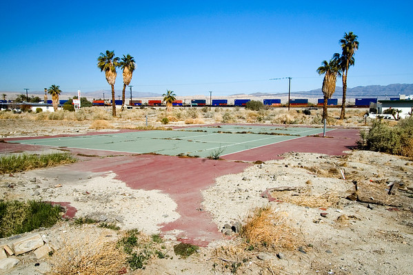 Former tennis courts with train passing in background.