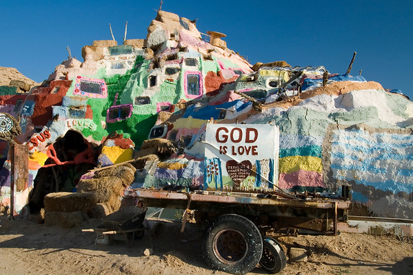 Cart and outside view of the museum, where Leonard continues to build and paint.  Leonard's work finally got the attention of senator Barbara Boxer, whose 2002 entry into the congressional record proclaimed Salvation Mountain a national treasure, and he even got a plaque to show for it.