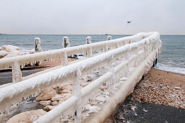 An iced up pier after a long run of frigid & windy winter days.  Iron Pier Beach, Jamesport, NY.