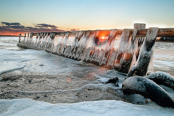 Sunset behind an iced up decaying pier in Amity Harbor, NY.