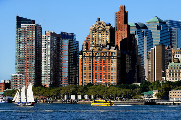Sailboat and Water Taxi passing by the tip of Lower Manhattan