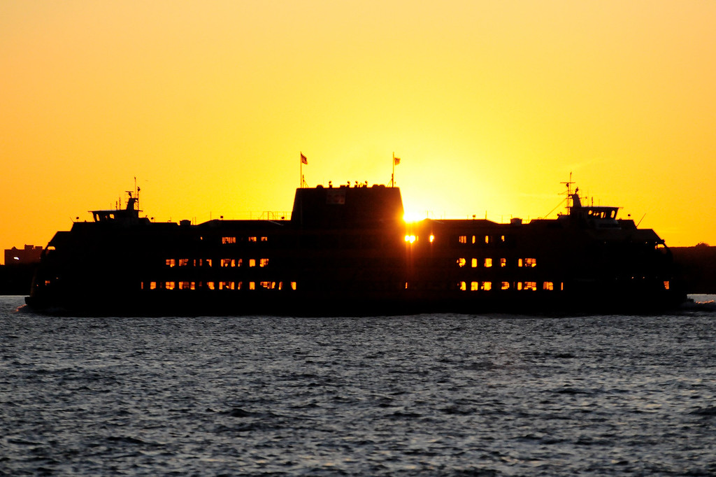 Staten Island Ferry with its windows lit up by the setting sun