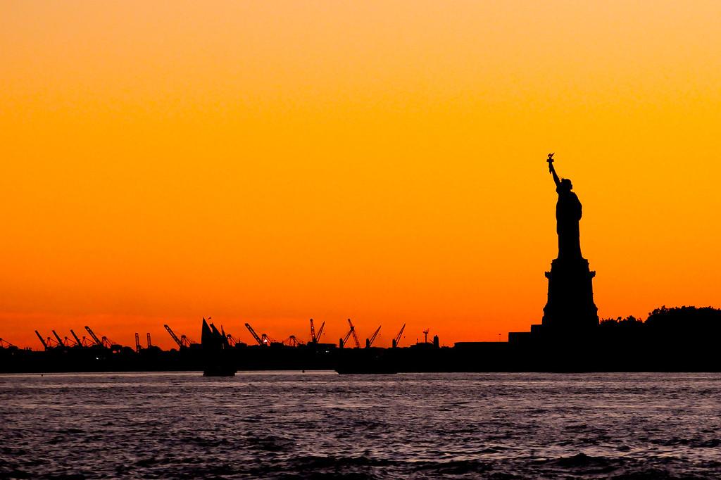 Statue of Liberty presiding over a golden NYC Harbor