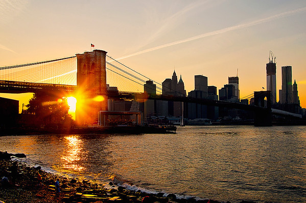 Sun setting behind the Brooklyn Bridge on a mid-October afternoon.  The Freedom Tower still under construction can be seen in the background.