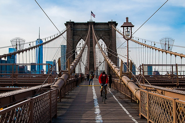Bicyclist crossing the Brooklyn Bridge into Brooklyn.  With newly completed Freedom Tower in the background