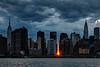 """""""Manhattanhenge"""", when the setting sun perfectly aligns with the east-to-west cross streets on Manhattan's grid, as seen from Hunter's Point/Queens on May 30, 2014."""
