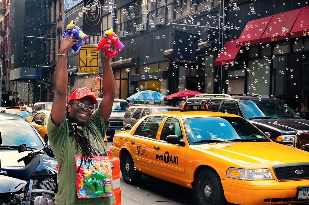 Vendor having fun shooting his bubble guns during a street fair on Broadway.