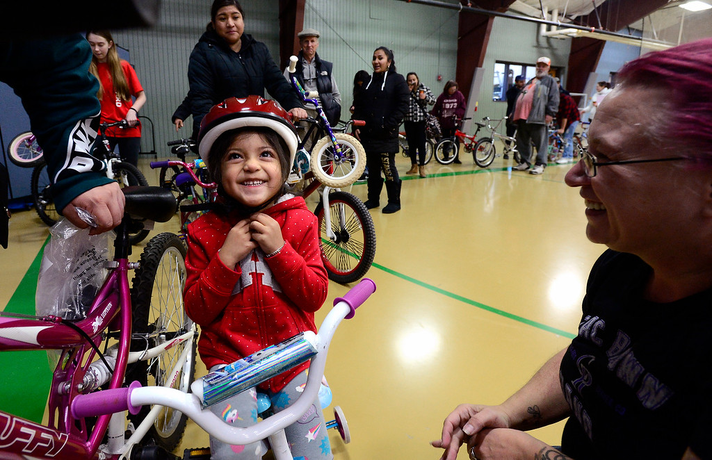 . LONGMONT, CO - DECEMBER 8, 2018  Melanie Flores, 3, smiles after volunteer Tabitha Keagle helped her fit her bicycle helmet during the Kids\' Holiday Bike Giveaway sponsored by Bicycle Longmont at the Ed & Ruth Lehman YMCA on Saturday in Longmont December 8, 2018.  For more photos go to timescall.com (Photo by Paul Aiken/Staff Photographer)