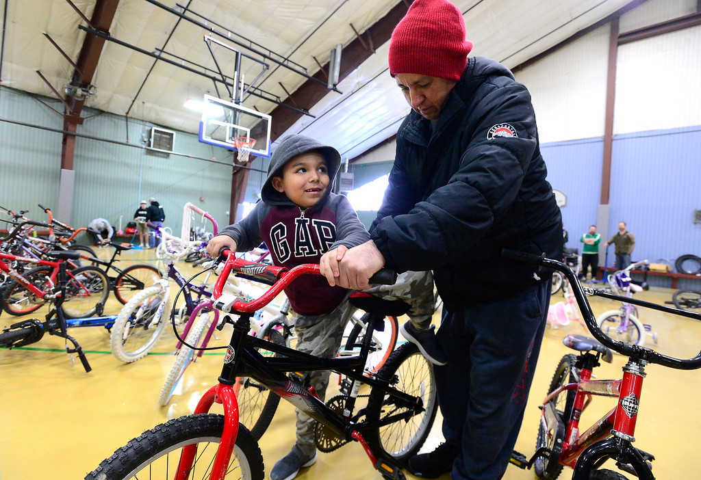 . LONGMONT, CO - DECEMBER 8, 2018  Oscar Savala helps his sone Jesus, 6, try out a bike during the Kids\' Holiday Bike Giveaway sponsored by Bicycle Longmont at the Ed & Ruth Lehman YMCA on Saturday in Longmont December 8, 2018.  For more photos go to timescall.com (Photo by Paul Aiken/Staff Photographer)