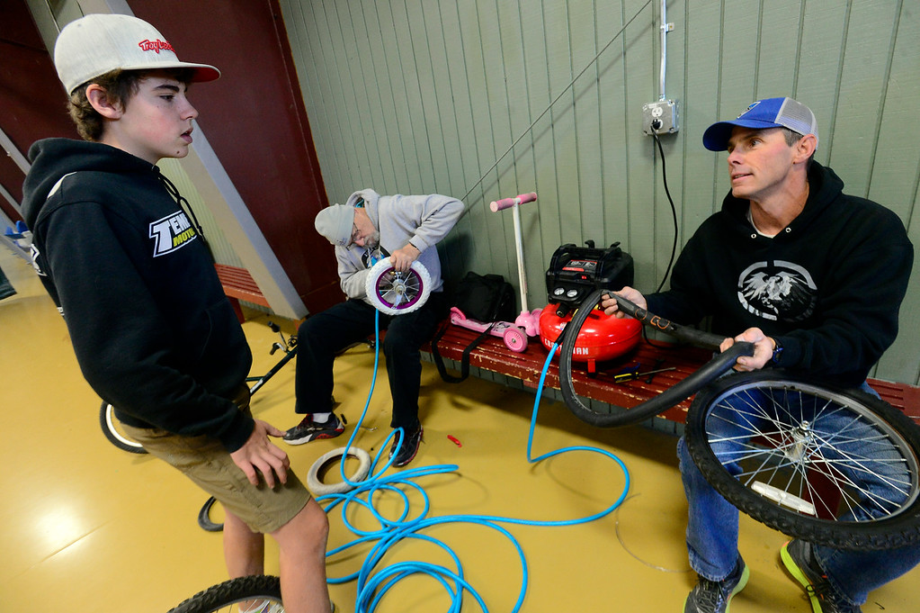 . LONGMONT, CO - DECEMBER 8, 2018  Darrin Cole and his son Bryce work on fixing bike tires for donated bikes during the Kids\' Holiday Bike Giveaway  sponsored by Bicycle Longmont at the Ed & Ruth Lehman YMCA on Saturday in Longmont December 8, 2018.  For more photos go to timescall.com (Photo by Paul Aiken/Staff Photographer)