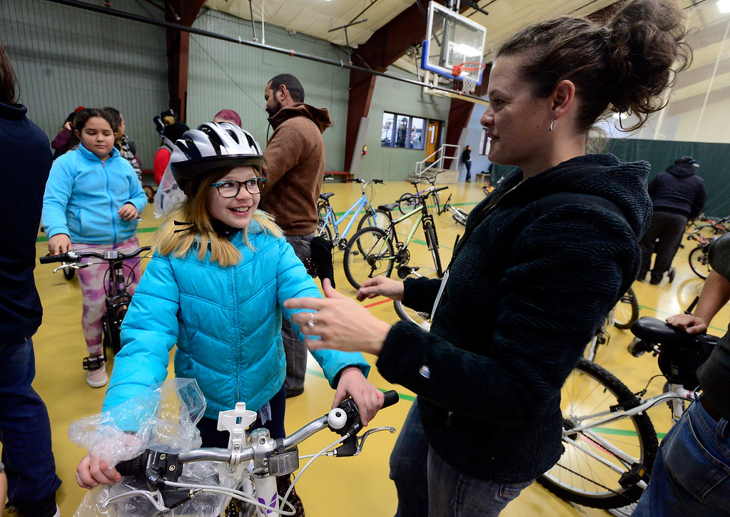 . LONGMONT, CO - DECEMBER 8, 2018  Bella Brewer, 9, shakes her head to make sure her new bike helmet fits with the help of volunteer Christy Willett during the Kids\' Holiday Bike Giveaway  sponsored by Bicycle Longmont at the Ed & Ruth Lehman YMCA on Saturday in Longmont December 8, 2018. Willett is a volunteer from the Longmont United Hospital Trauma Department which donated a helmet to each bike that was given away.  For more photos go to timescall.com (Photo by Paul Aiken/Staff Photographer)