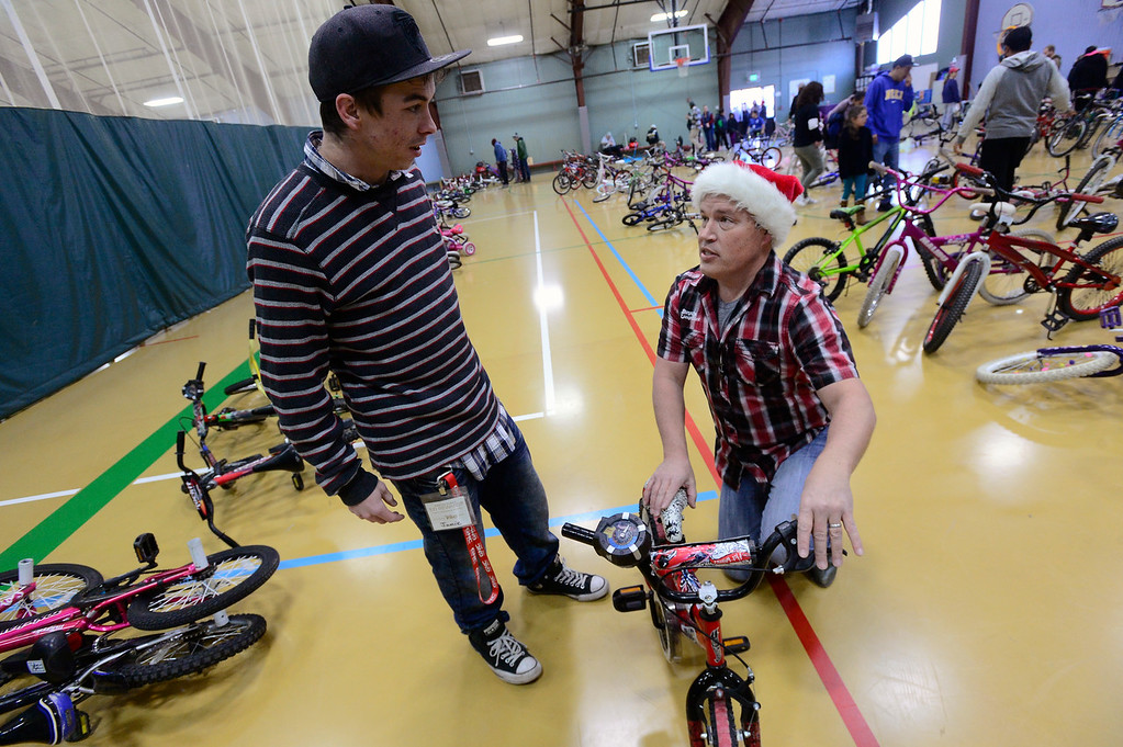 . LONGMONT, CO - DECEMBER 8, 2018  Roger Santistevan, left, gets advice about the bike he is getting for his son Landon from Ryan Kragerud of Bicycle Longmont during the Kids\' Holiday Bike Giveaway  at the Ed & Ruth Lehman YMCA on Saturday in Longmont December 8, 2018.  For more photos go to timescall.com (Photo by Paul Aiken/Staff Photographer)