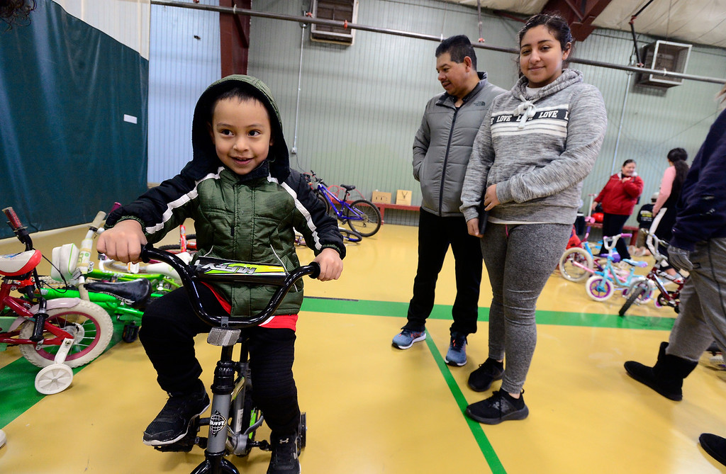 . LONGMONT, CO - DECEMBER 8, 2018  Brandon Perez, 5, takes off on his new bike as his dad Francisco and sister Shaila look on during the Kids\' Holiday Bike Giveaway  sponsored by Bicycle Longmont at the Ed & Ruth Lehman YMCA on Saturday in Longmont December 8, 2018.  For more photos go to timescall.com (Photo by Paul Aiken/Staff Photographer)