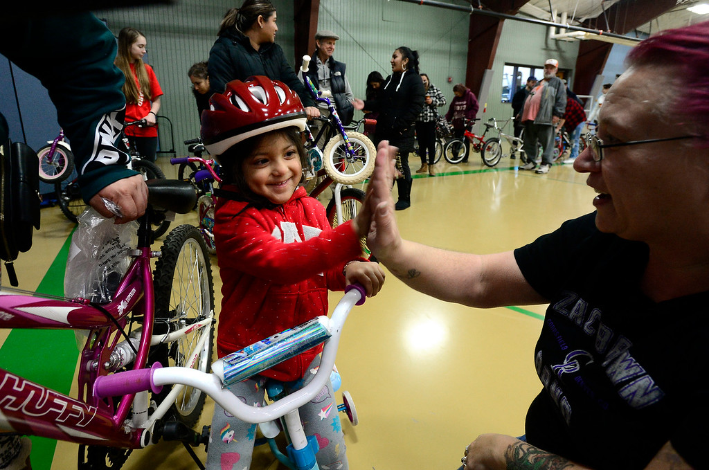. USE THIS ONE LONGMONT, CO - DECEMBER 8, 2018  Melanie Flores, 3, smiles after volunteer Tabitha Keagle helped her fit her bicycle helmet during the Kids\' Holiday Bike Giveaway sponsored by Bicycle Longmont at the Ed & Ruth Lehman YMCA on Saturday in Longmont December 8, 2018.  For more photos go to timescall.com (Photo by Paul Aiken/Staff Photographer)