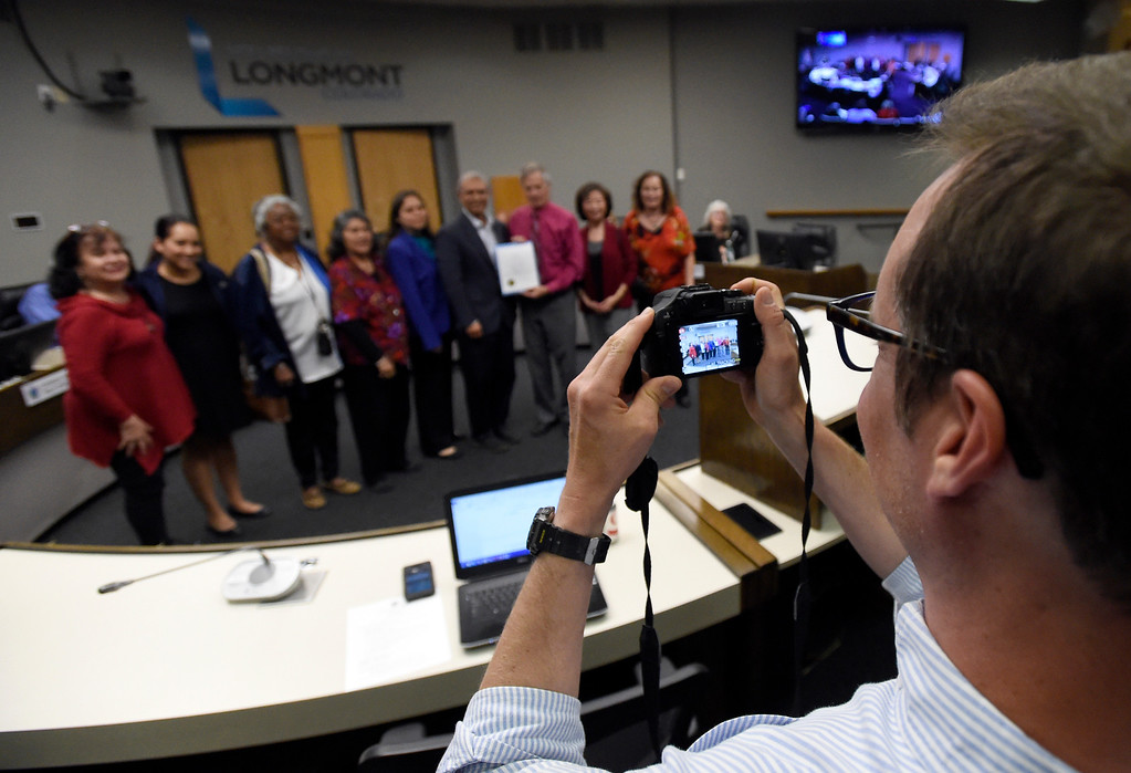 """. Assistant City Manager Shawn Lewis takes a photograph of Mayor Dennis Coombs and a group of community members as they hold a Proclamation designating May 21, 2017 as \"""" World Day for Cultural Diversity for Dialogue and Development\"""" during public comment regarding the issue of becoming a sanctuary city during a Longmont City Council meeting in the Civic Center on Tuesday in Longmont. For more photos of the City Council meeting go to www.dailycamera.com Jeremy Papasso/ Staff Photographer/ May 16, 2017"""