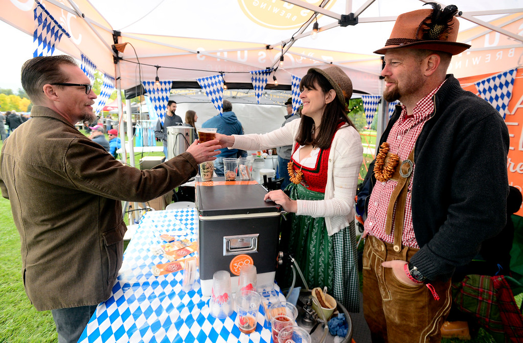 . LONGMONT, CO OCTOBER 6 2018 Thomas Buettner gets a beer from Jean and Dan Ditslear owners of 300 Suns Brewing at Longmont Oktoberfest on Saturday.  (Photo by Paul Aiken/Staff Photographer)