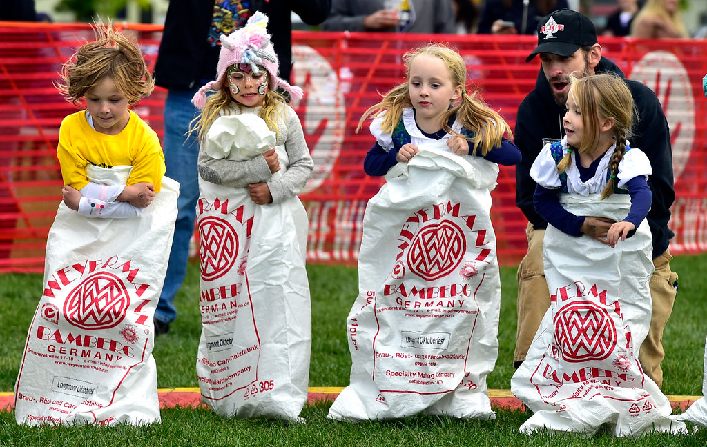 . LONGMONT, CO OCTOBER 6 2018 From left to right Addie Loseke, Annabell Hendricks, and twins Stella and Adrienne Merk heads away from the start line during the sack race at Longmont Oktoberfest on Saturday.  (Photo by Paul Aiken/Staff Photographer)