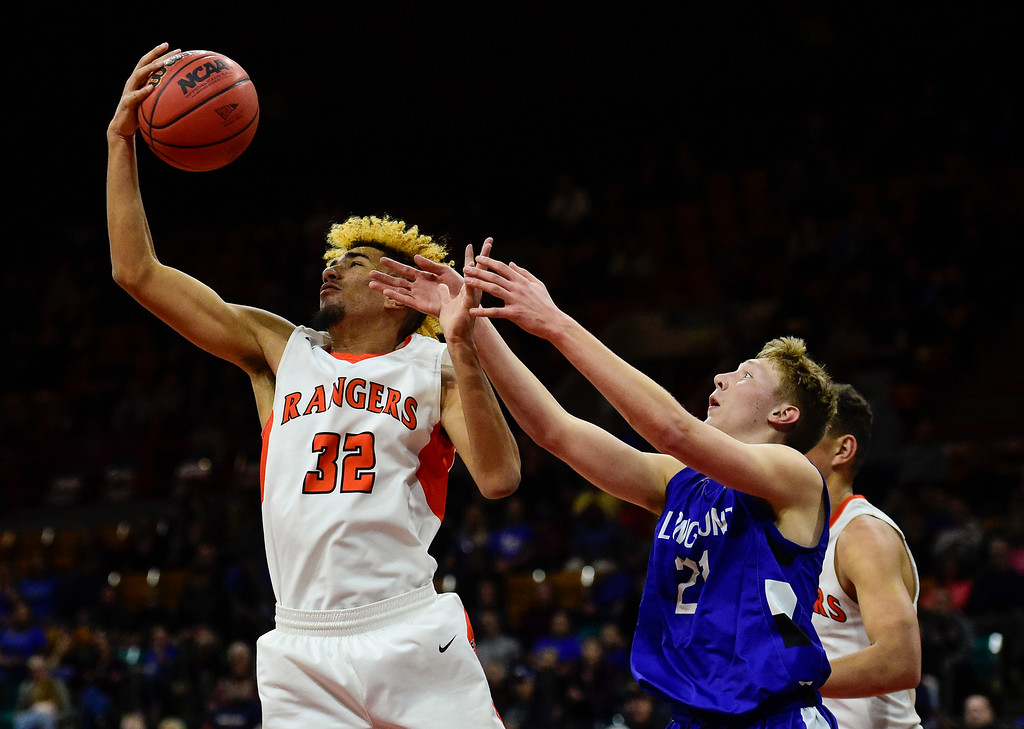 . DENVER, CO - MARCH 9:Longmont High School\'s Dallas Dye (No. 21) battle for a rebound with Lewis Palmer High School\'s Tre McCullough (No. 32) during the 4A state basketball final at the Denver Coliseum on March 9, 2019. The Trojans were defeated by the Rangers, 57-52. (Photo by Matthew Jonas/Staff Photographer)