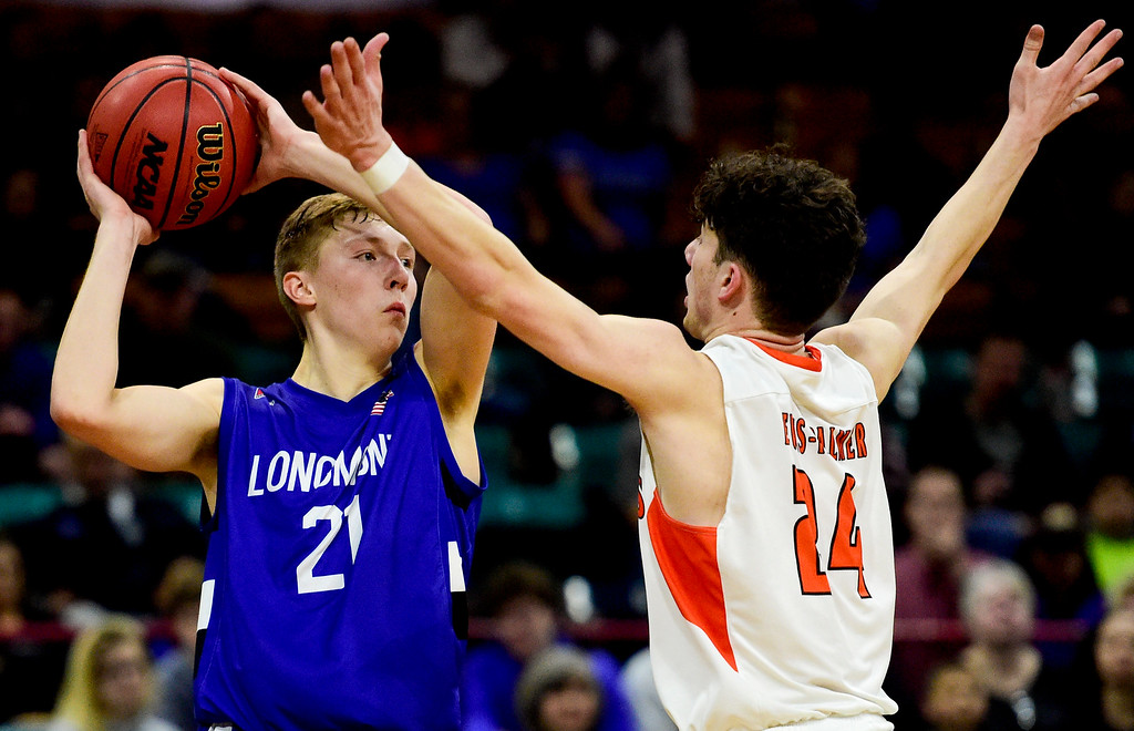 . DENVER, CO - MARCH 9:Longmont High School\'s  Dallas Dye (No. 21) looks to pass while covered by Lewis Palmer High School\'s Dominic Roma (No. 24) during the 4A state basketball final at the Denver Coliseum on March 9, 2019. The Trojans were defeated by the Rangers, 57-52. (Photo by Matthew Jonas/Staff Photographer)