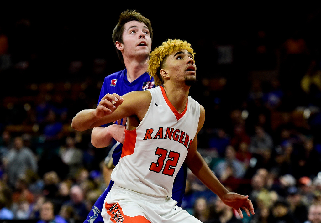 . DENVER, CO - MARCH 9:Lewis Palmer High School\'s Tre McCullough (No. 32) tries to box out Longmont High School\'s Calvin Seamons (No. 35) during the 4A state basketball final at the Denver Coliseum on March 9, 2019. The Trojans were defeated by the Rangers, 57-52. (Photo by Matthew Jonas/Staff Photographer)