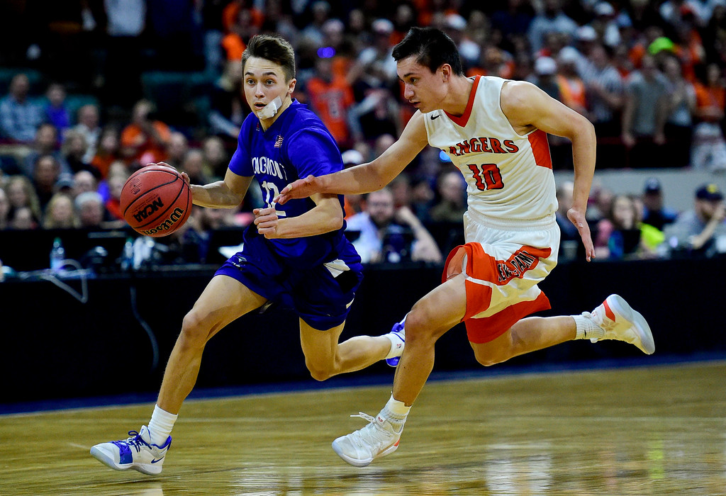 . DENVER, CO - MARCH 9:Longmont High School\'s Brady Renck (No. 12) drives around Lewis Palmer High School\'s Noah Baca (No. 10) during the 4A state basketball final at the Denver Coliseum on March 9, 2019. The Trojans were defeated by the Rangers, 57-52. (Photo by Matthew Jonas/Staff Photographer)