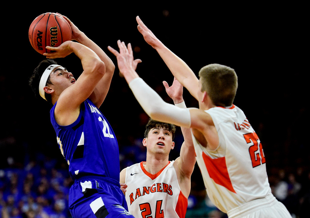 . DENVER, CO - MARCH 9:Longmont High School\'s Oakley Dehning (No. 22) shoots over Lewis Palmer High School\'s Matthew Ragsdale (No. 22) and Dominic Roma (No. 24) during the 4A state basketball final at the Denver Coliseum on March 9, 2019. The Trojans were defeated by the Rangers, 57-52. (Photo by Matthew Jonas/Staff Photographer)
