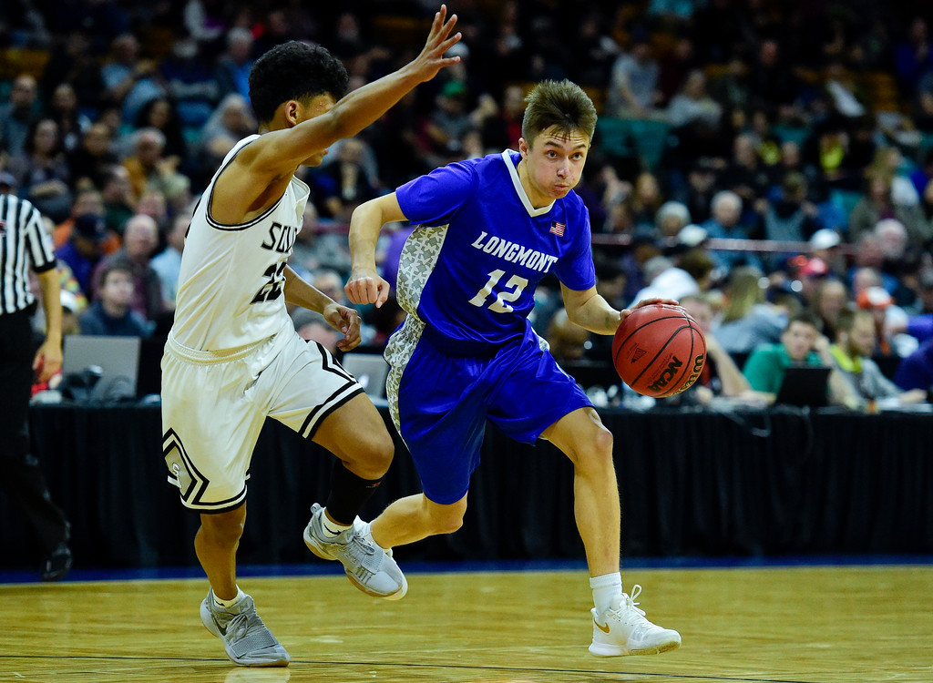 . Longmont High School\'s Brady Renck (No. 12) drives around Pueblo South High School\'s Tonay Aragon (No. 22) in the class 4A state basketball final four game at the Denver Coliseum in Denver, Colorado on March 9, 2018. (Photo by Matthew Jonas/Staff Photographer)