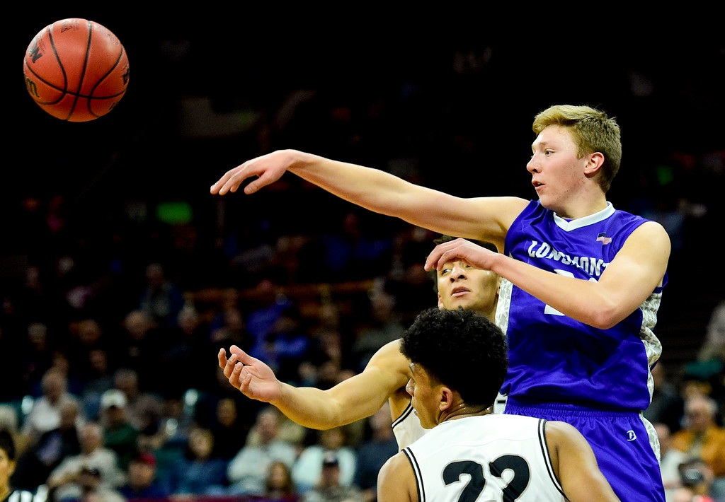 . Longmont High School\'s Dallas Dye (No. 21) passes the ball over Pueblo South High School\'s Tonay Aragon (No. 22) and Marcell Barbee (No. 11) in the class 4A state basketball final four game at the Denver Coliseum in Denver, Colorado on March 9, 2018. (Photo by Matthew Jonas/Staff Photographer)