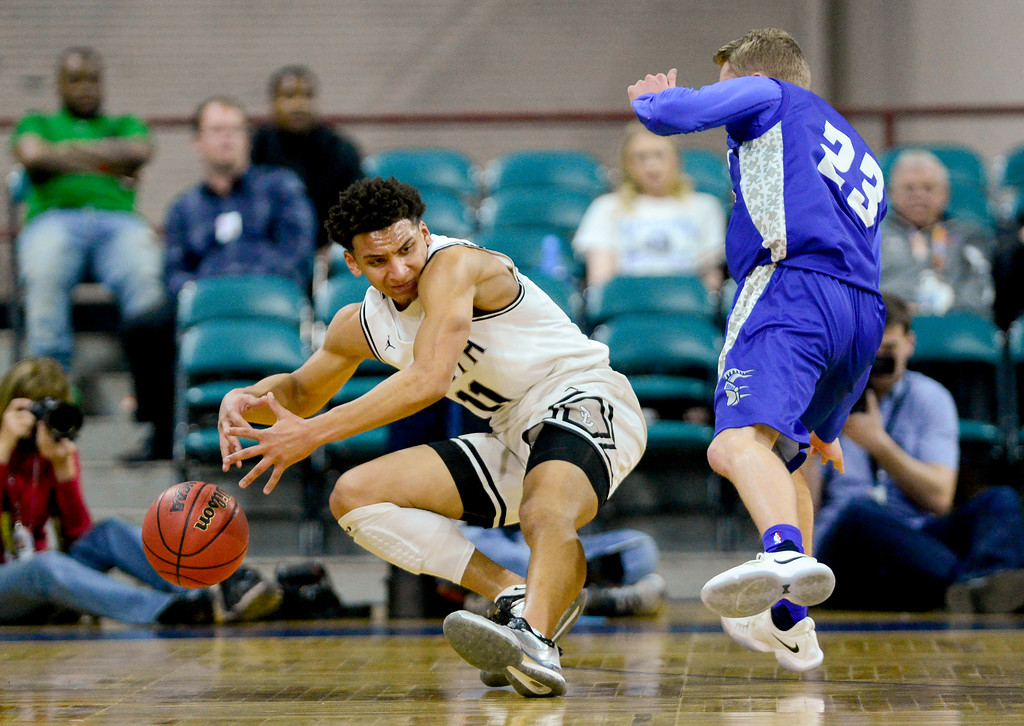 . Pueblo South High School\'s Marcell Barbee (No. 11) falls down under pressure from Longmont High School\'s Caden Dion (No. 23) in the class 4A state basketball final four game at the Denver Coliseum in Denver, Colorado on March 9, 2018. (Photo by Matthew Jonas/Staff Photographer)