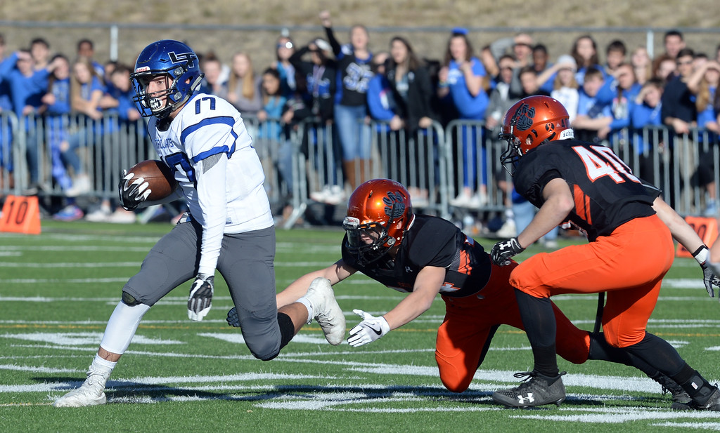 . Sage Yazzie, of Longmont, tries to escape the Erie defenders during the 3A semifinals at Erie High School on Saturday. For more photos, go to BoCoPreps.com  Cliff Grassmick / Staff Photographer/ November 25, 2017, 2017