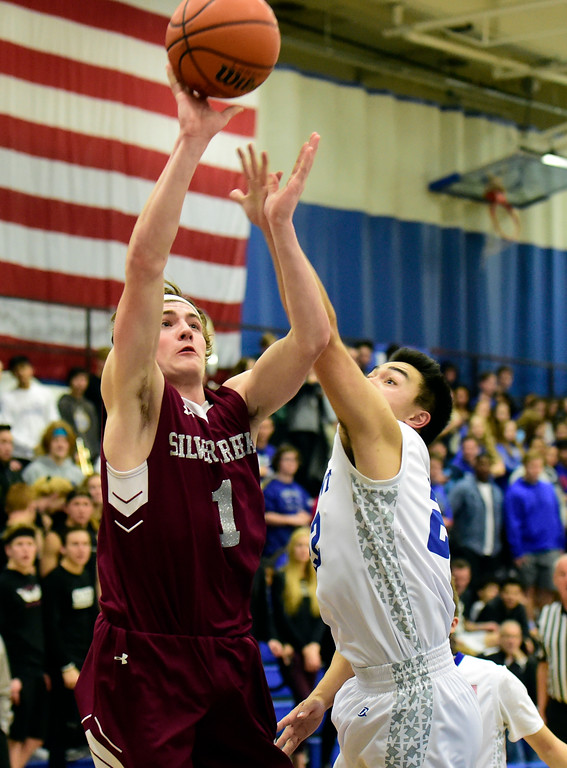 . Silver Creek High School\'s Nick Eaton takes a shot over Oakley Dehning during a game against Longmont on Thursday in Longmont. More photos: BoCoPreps.com Jeremy Papasso/ Staff Photographer 02/08/2018