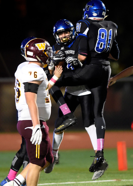 . LONGMONT, CO - OCTOBER 11, 2018: Longmont High School\'s Sage Yazzie, center, is congratulated on a touchdown by teammate Dallas Dye during a CHSAA football game against Windsor on Thursday in Longmont. More photos: BoCoPreps.com (Photo by Jeremy Papasso/Staff Photographer)