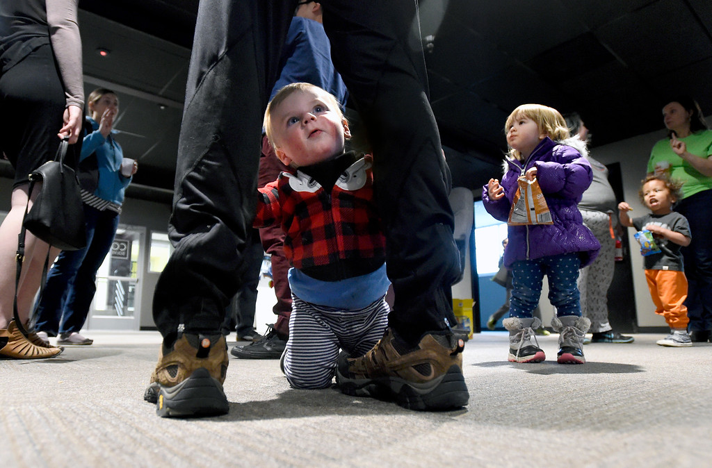 . Kevin Winter\'s one-year-old son Logan peeks through his legs during the grand opening of the new CoSolve coworking space on Friday at 350 Terry Street in Longmont. For more photos of the grand opening go to dailycamera.com Jeremy Papasso/ Staff Photographer 04/13/2018
