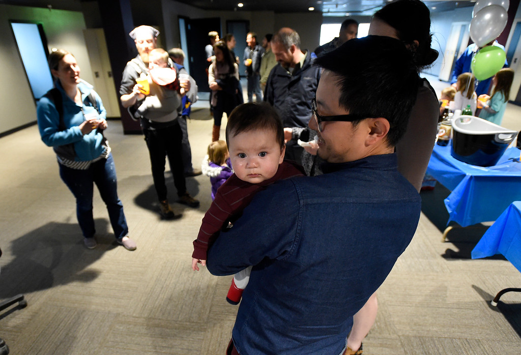 . Peng Fan holds his seven-month-old daughter Quinn during the grand opening of the new CoSolve coworking space on Friday at 350 Terry Street in Longmont. For more photos of the grand opening go to dailycamera.com Jeremy Papasso/ Staff Photographer 04/13/2018