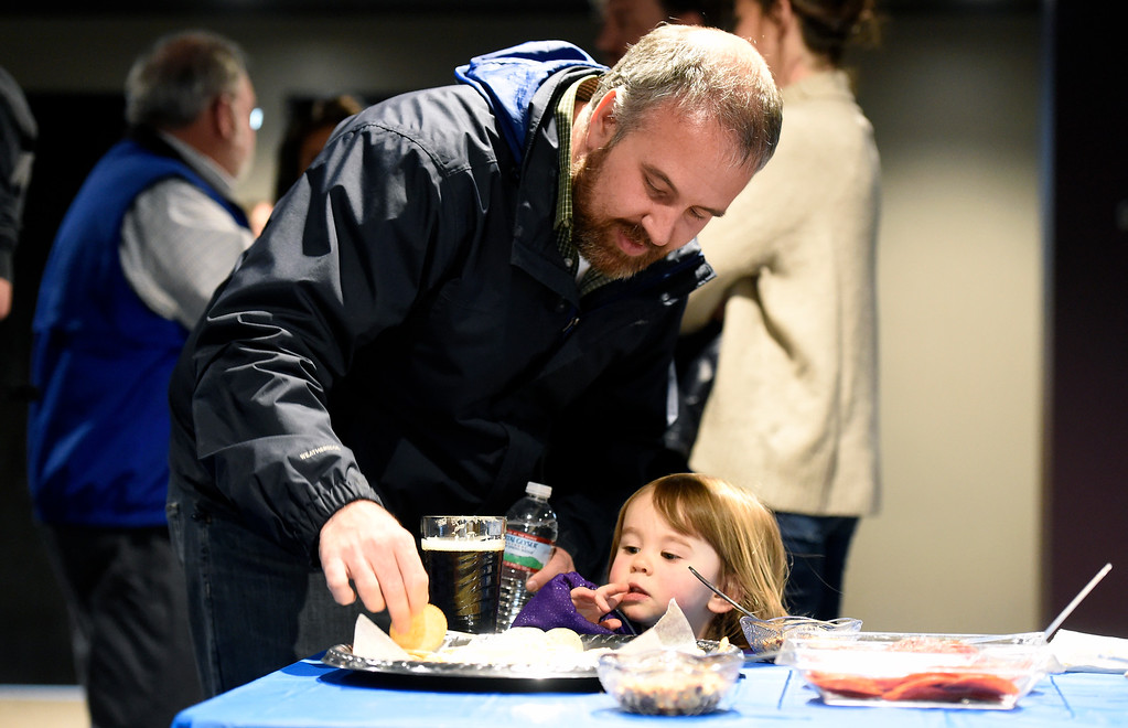 . Matt Elder, of Longmont, gives his daughter Madeleine, 2, a cracker during the grand opening of the new CoSolve coworking space on Friday at 350 Terry Street in Longmont. For more photos of the grand opening go to dailycamera.com Jeremy Papasso/ Staff Photographer 04/13/2018