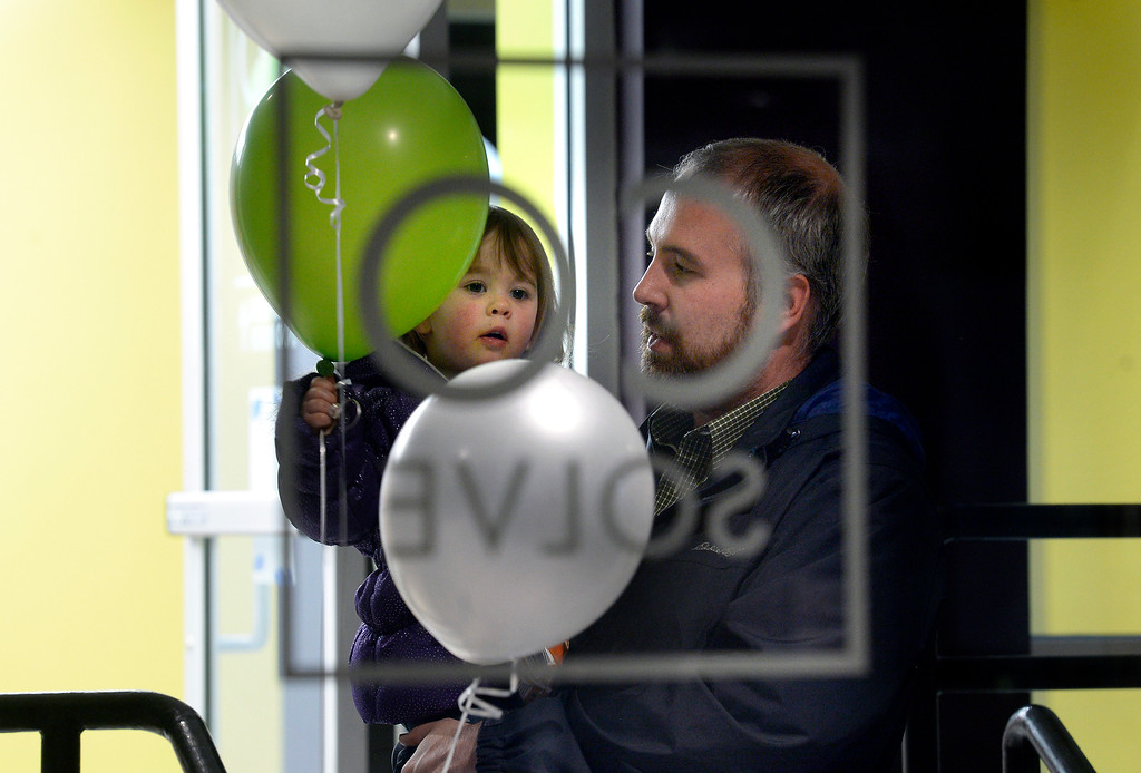 . Matt Elder, of Longmont, holds his daughter Madeleine, 2, while she plays with balloons during the grand opening of the new CoSolve coworking space on Friday at 350 Terry Street in Longmont. For more photos of the grand opening go to dailycamera.com Jeremy Papasso/ Staff Photographer 04/13/2018