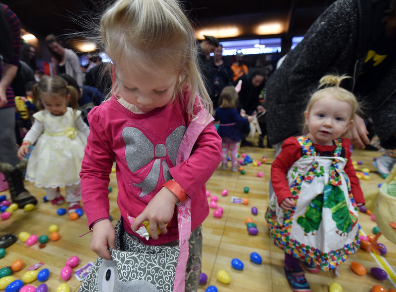 "Grace Pearl, 3, gathers eggs and candy placing them in her satchel during the Easter Egg Hunt at the Longmont Memorial Center on Saturday sponsored by the White Fields Church.<br /> More photos:  <a href=""http://www.BoCoPreps.com"">http://www.BoCoPreps.com</a><br /> David R. Jennings/Staff Photographer<br /> March 26, 2016"