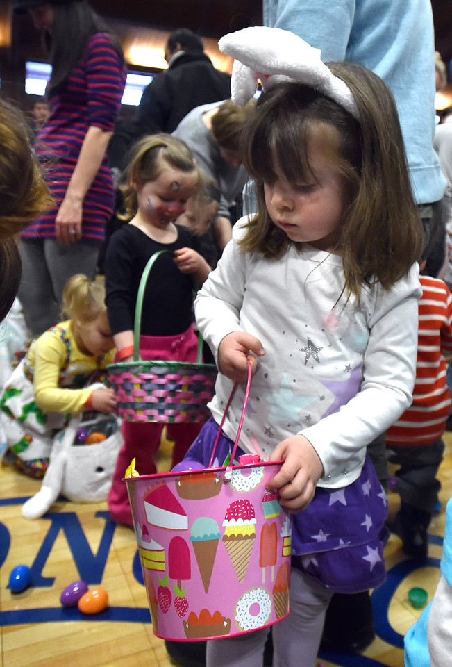 "Jenette Chinnis, 3, gathers eggs and candy placing them in her basket during the Easter Egg Hunt at the Longmont Memorial Center on Saturday sponsored by the White Fields Church.<br /> More photos:  <a href=""http://www.BoCoPreps.com"">http://www.BoCoPreps.com</a><br /> David R. Jennings/Staff Photographer<br /> March 26, 2016"