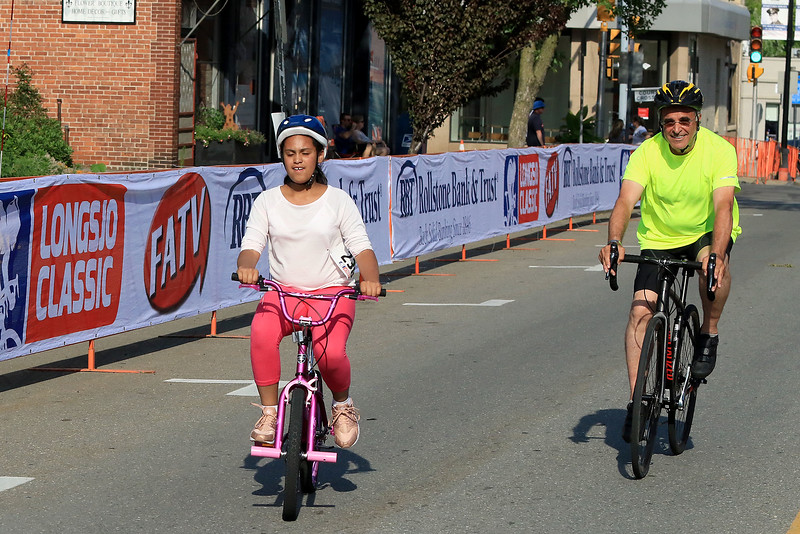 Leominster Mayor Dean Mazzarella rides next to Micheycka Disdier, 10, of Leominster in one of the kids races during the Longsjo Classic on Saturday. SENTINEL & ENTERPRISE/JOHN LOVE