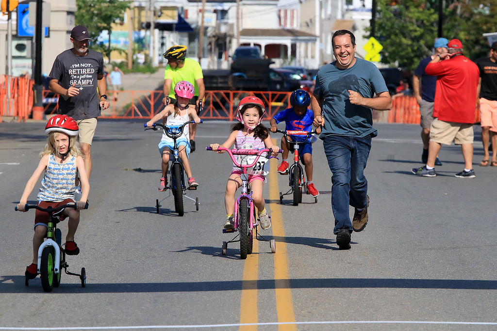 . John Haley runs next to his daughter Hannah Haley, 5, from Leominster as she competes in one of the kids races during the Longsjo Classic on Saturday in Leominster. SENTINEL & ENTERPRISE/JOHN LOVE