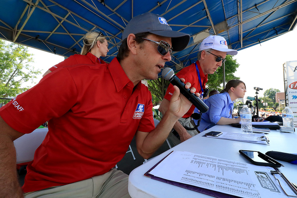 . Announcer Frankie Andreu talks about the riders as they speed by the starting/finish line during the Longsjo Classic in Leominster on Saturday. SENTINEL & ENTERPRISE/JOHN LOVE