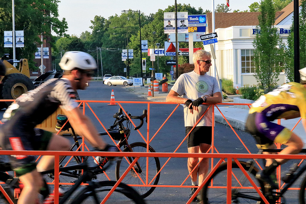 . A guy out on his bike stop on Main Street to watch the riders go by in the Men\'s Pro Cat 1/2 race during the first day of the Longsjo Classic in Leominster on Saturday. SENTINEL & ENTERPRISE/JOHN LOVE