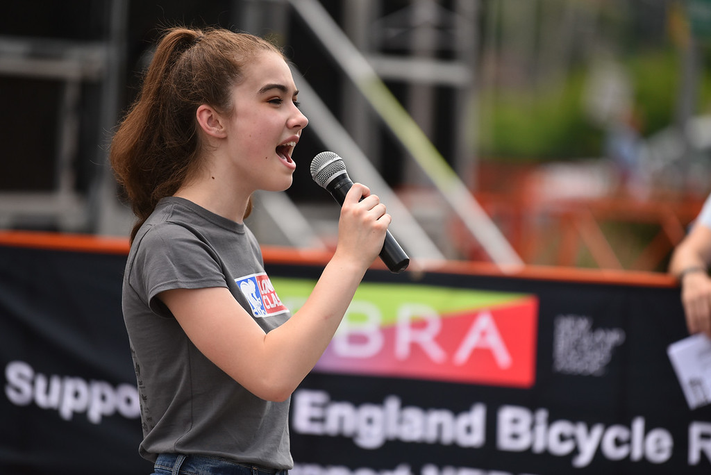 . Mary Mahoney, 15, of Fitchburg sings the National Anthem at the start of the 2018 Longsjo Classic in Fitchburg on Sunday.  SENTINEL & ENTERPRiSE JEFF PORTER