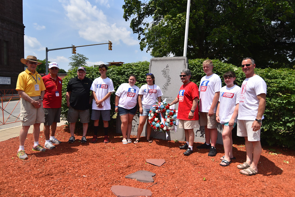 . Race officials alongside city officials place a wreathe on the Longsjo memorial during the 2018 Longsjo Classic in Fitchburg on Sunday.  SENTINEL & ENTERPRiSE JEFF PORTER
